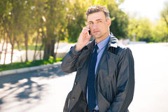 Thoughtful businessman talking on the phone outdoors Stock Photography