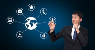 Thoughtful businessman touching digitally generated technology icons Royalty Free Stock Images
