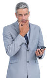 Thoughtful businessman touching his chin holding cellphone Stock Images