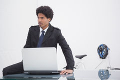 Thoughtful businessman in trench coat using laptop Stock Image