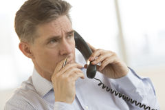 Thoughtful Businessman Using Landline Phone In Office Stock Photo