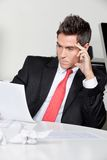 Thoughtful Businessman Working At Desk. Thoughtful young businessman working at desk in office Royalty Free Stock Photography