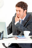 Thoughtful businessman working on laptop in office Stock Images