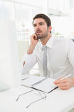 Thoughtful businessman writing on notepad royalty free stock image
