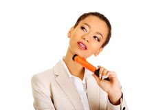 Thoughtful businesswoman with big pen. Stock Photo