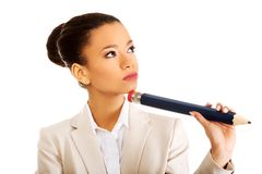 Thoughtful businesswoman with big pencil. Stock Photo