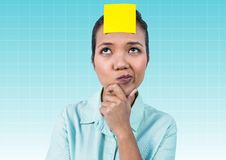 Thoughtful businesswoman with blank yellow sticky note on forehead. Against blue background Royalty Free Stock Images