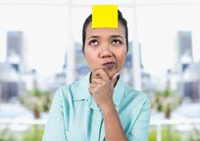 Thoughtful businesswoman with blank yellow sticky note on forehead. In office Stock Photography