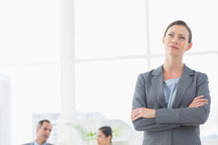 Thoughtful businesswoman with colleagues behind Royalty Free Stock Image
