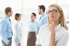 Thoughtful businesswoman with colleagues behind Royalty Free Stock Photography