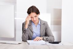 Thoughtful businesswoman doing calculations Stock Photography