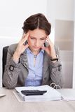 Thoughtful businesswoman doing calculations Stock Photos