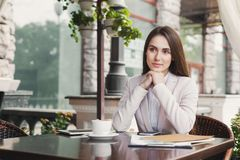 Young businesswoman outdoors drinking coffee. Thoughtful businesswoman drinking coffee, sitting at summer terrace cafe. Lifestyle portrait of young business Stock Photos