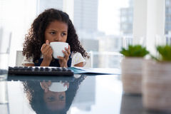 Thoughtful businesswoman having coffee while sitting at desk Stock Image