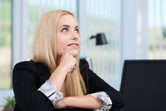 Thoughtful businesswoman at her desk Royalty Free Stock Photos