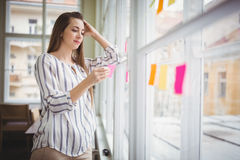 Thoughtful businesswoman holding adhesive note by window in creative office Stock Photography