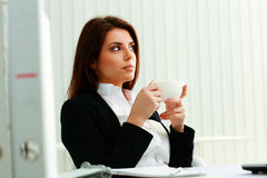 Thoughtful businesswoman holding cup and looking up Royalty Free Stock Photos