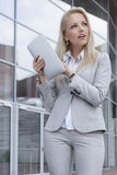 Thoughtful businesswoman holding digital tablet while looking away against office building Stock Photos