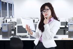 Thoughtful businesswoman holding digital tablet Stock Photo