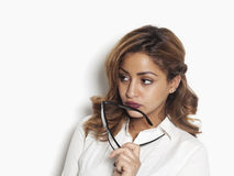 Thoughtful businesswoman holding glasses Royalty Free Stock Image
