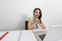 Thoughtful businesswoman holding pen under nose at desk in office Stock Photos
