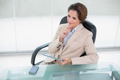 Thoughtful businesswoman holding tablet at her desk Stock Photos