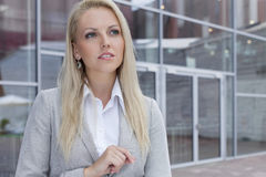 Thoughtful businesswoman looking away against office building Stock Photography