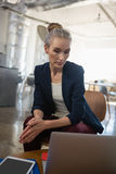 Thoughtful businesswoman looking down while sitting on chair Royalty Free Stock Image