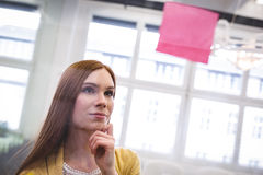 Thoughtful businesswoman looking on pink sticky note. On glass in creative office Royalty Free Stock Photo