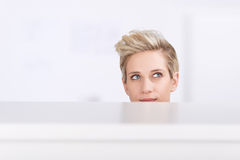 Thoughtful Businesswoman Looking Up In Office Cubicle. Young businesswoman looking up while daydreaming in office cubicle Royalty Free Stock Photos