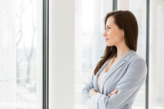 Thoughtful businesswoman looking through window in office Royalty Free Stock Image