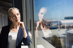 Thoughtful businesswoman looking through window at office Royalty Free Stock Photos
