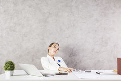 Thoughtful businesswoman in office. Thoughful daydreaming businesswoman sitting at office desk with laptop, plant, smartphone, paperwork and other items Stock Image