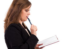 Thoughtful businesswoman with organizer and a pen. Against white background Stock Images