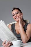 Thoughtful businesswoman read newspaper at office Stock Photography