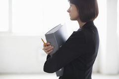 Thoughtful Businesswoman With Ring Binder Royalty Free Stock Photography