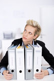 Thoughtful Businesswoman With Ring Binders At Desk Royalty Free Stock Photo