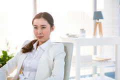 Thoughtful businesswoman sitting on a chair Stock Image
