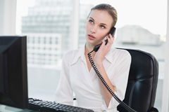 Thoughtful businesswoman sitting at desk on the phone Royalty Free Stock Photo