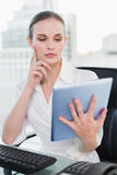 Thoughtful businesswoman sitting at desk using tablet pc Royalty Free Stock Photography