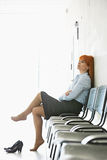 Thoughtful businesswoman sitting with legs crossed on chair in office Royalty Free Stock Photo