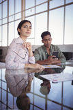 Thoughtful businesswoman sitting with male colleague using mobile phone Royalty Free Stock Image