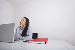 Thoughtful businesswoman sitting at office desk Stock Photo
