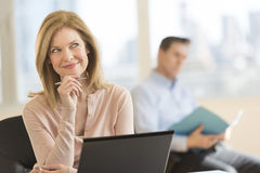 Thoughtful Businesswoman Smiling In Office Stock Photography