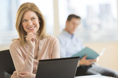 Thoughtful Businesswoman Smiling In Office Royalty Free Stock Images