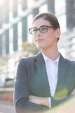 Thoughtful businesswoman standing arms crossed outdoors Stock Photo