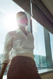 Thoughtful businesswoman standing by brightly lit window in office Royalty Free Stock Photo