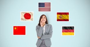 Thoughtful businesswoman standing by flags against blue background stock images