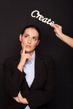 Thoughtful businesswoman standing under CREATE Royalty Free Stock Photography