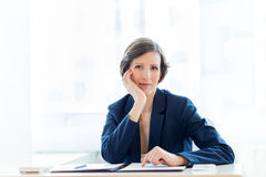 Thoughtful businesswoman staring pensively ahead. At the camera with her chin resting on her hand as she sits at a desk in the office working on documents Royalty Free Stock Images